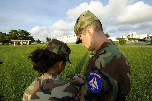 Senior Airman Chance Sheek (right), an 18th Logistics Readiness Squadron vehicle operator, teaches a young cadet in the Civil Air Patrol how to use a compass on Kadena Air Base, Japan, June 26, 2015. Sheek is now a first lieutenant in the CAP and is held responsible for ground emergency training such as search and rescue. (U.S. Air Force photo/Airman 1st Class Zackary A. Henry)