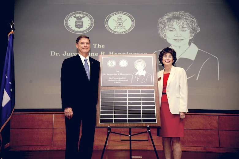 Kevin E. Williams, Director, Air Force Studies, Analyses and Assessments, and Dr. Jacqueline R. Henningsen unveil the Air Force Analyst Lifetime Achievement Award renamed after Dr. Henningsen at the Mark Center, Arlington, Va., June 25, 2015. (U.S. Air force photo/Staff Sgt. Whitney Stanfield)