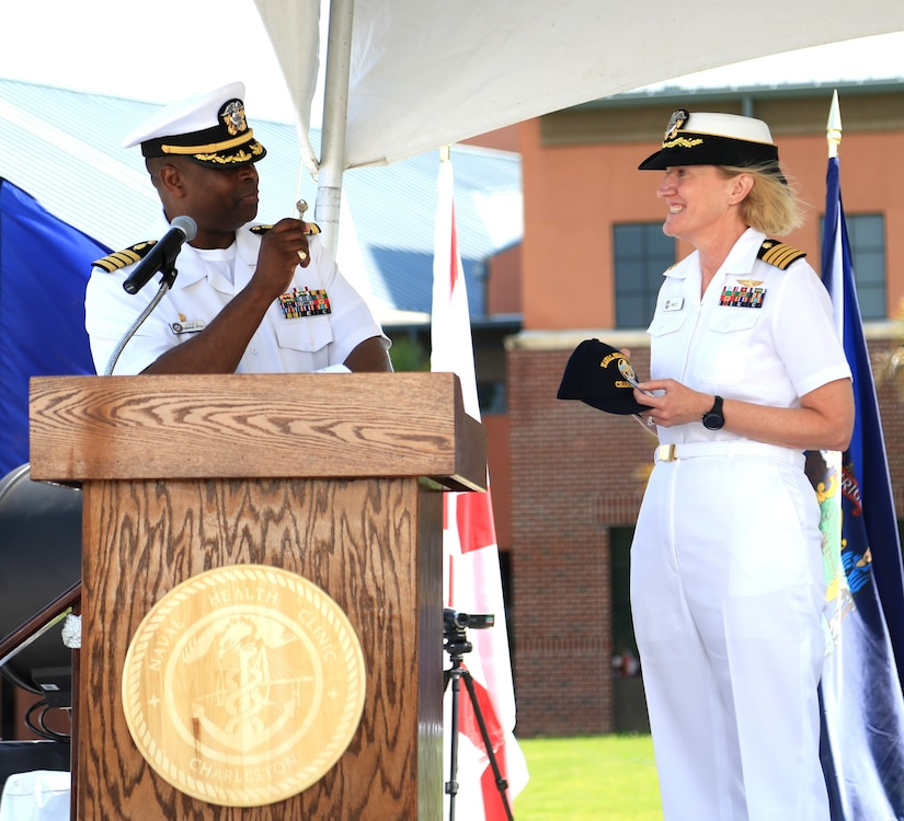 Captain Marvin Jones, outgoing commanding officer of Naval Health Clinic Charleston, presents Capt. Elizabeth Maley, incoming commanding officer, the key to NHCC as he relinquishes command to Maley during a change of command ceremony June 26, 2015 at the clinic on Joint Base Charleston - Weapons Station. Jones, a healthcare administrator, is leaving NHCC to be the base commander at Naval Support Activity in Bethesda, MD. Maley, an occupational health physician, comes to NHCC from Naval Health Clinic Cherry Point, N.C., where she served as executive officer for two years. (Navy photo/ Hospitalman Adrienne Quinter)