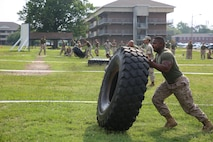 Lance Cpl. Corey Banks, machine gunner, Weapons Company, Ground Combat Element Integrated Task Force, competes in the tire flip challenge as part of the task force field meet outside of the Command Post, July 2, 2015. From October 2014 to July 2015, the GCEITF conducted individual and collective level skills training in designated ground combat arms occupational specialties in order to facilitate the standards based assessment of the physical performance of Marines in a simulated operating environment performing specific ground combat arms tasks. (U.S. Marine Corps photo by Cpl. Paul S. Martinez/Released)