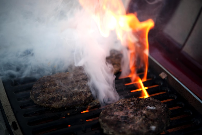 A grill flairs up while burgers cook during the 4th of July party at the Goodfellow Recreational Camp, Texas, July 4, 2015. During the celebration, team Goodfellow members enjoyed barbeque, live music and fireworks. (U.S. Air Force photo by Senior Airman Scott Jackson/Released)