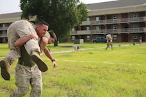 Capt. Michael Trumm, logistics officer, Headquarters and Service Company, Ground Combat Element Integrated Task Force, carries Lance Cpl. John Hash, armorer, H&S Co., GCEITF, as part of the task force field meet outside of the Command Post, July 2, 2015. From October 2014 to July 2015, the GCEITF conducted individual and collective level skills training in designated ground combat arms occupational specialties in order to facilitate the standards based assessment of the physical performance of Marines in a simulated operating environment performing specific ground combat arms tasks. (U.S. Marine Corps photo by Cpl. Paul S. Martinez/Released)