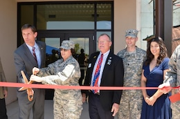 KIRTLAND AIR FORCE BASE, N.M. – District Commander Lt. Col. Patrick Dagon, second from right, watches as Sen. Martin Heinrich, far left, and Maj. Gen. Sandra Finan, commander of the Air Force Nuclear Weapons Center, cut the ribbon to officially open Phase 1 of the Air Force Nuclear Weapons Center expansion, June 29, 2015.