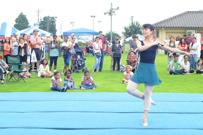 A dancer performs for members of Team Yokota during Celebrate America at Yokota Air Base, Japan, July 2, 2015. The 374th Force Support Squadron hosted events throughout the day to include a 5k Fun Run, the Leaky Kon Tiki race, go-karts, carnival booths and performances from the Band of the Pacific-Hawaii 'Hana Hou!'. (U.S. Air Force photo by Airman 1st Class David C. Danford/Released)