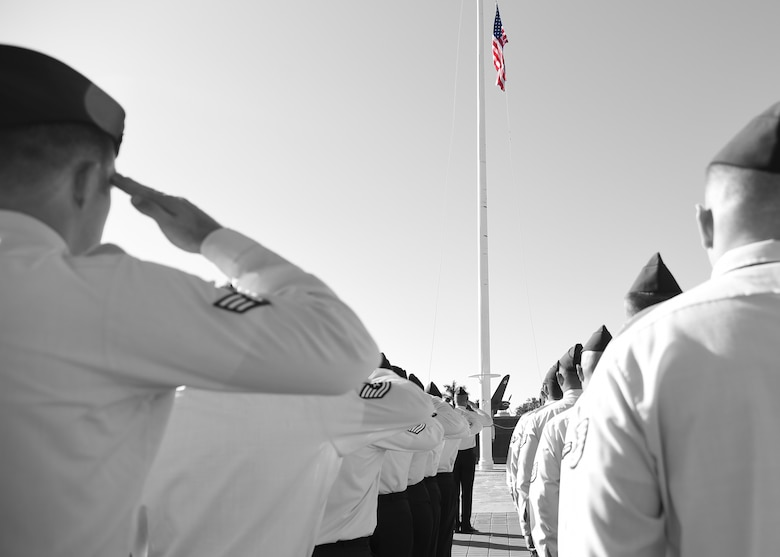 Members of the 747th Communications Squadron salute the U.S. flag during a Reveille ceremony on Joint Base Pearl Harbor-Hickam, Hawaii, July 2, 2015.The ceremony was performed by 60 Airmen from the 747th in honor of Independence Day. (U.S. Air Force illustration by Tech. Sgt. Aaron Oelrich/Released)