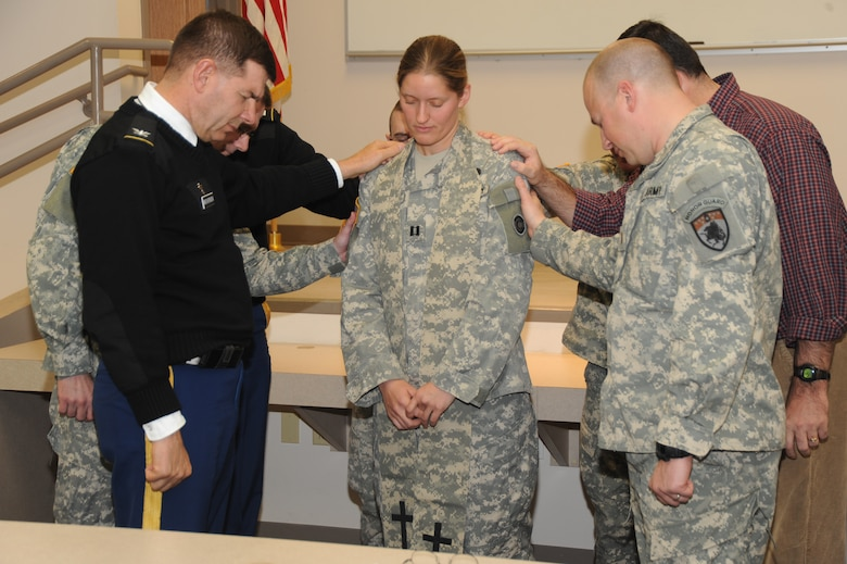 Colorado Army National Guard Chaplains surround Chaplain (Capt.) Mary St. Onge in prayer for her strength and to remind her she's not alone in her ministry, at the Colorado National Guard headquarters in Centennial, Colo. As of Dec. 1, 2010, St. Onge is the COARNG's newest chaplain and first female to hold the position in the entire CONG. St. Onge is assigned to the 193rd Military Police Battalion. (Official U.S. Air Force photo by Master Sgt. Cheresa D. Theiral, Colorado National Guard)