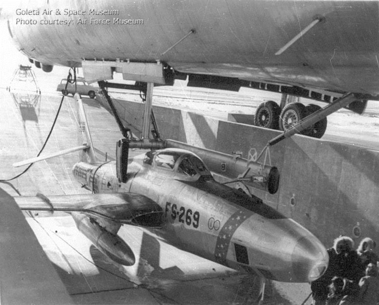 FICON RBF-84K Thunderflash, 52-7269, is lowered from the bomb bay of GRB-36D Peacemaker, 49-2696, at Fairchild Air Force Base, Wash., following an emergency night retrieval on Dec. 12, 1955. The parasite pilot suffered a partial hydraulic system failure but succeeded in hooking onto the trapeze. Post-flight inspection revealed he had turned off his own hydraulic system due to the distractions of approaching the trapeze. (U.S. Air Force photo)