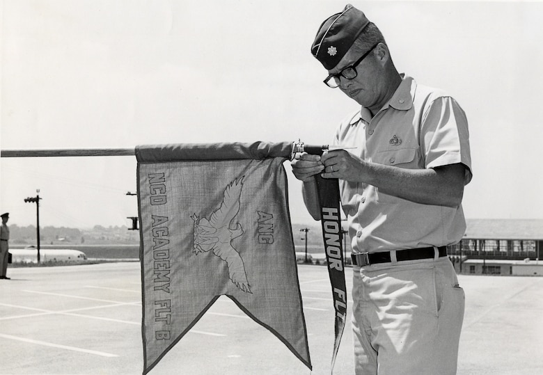 MCGHEE TYSON AIR NATIONAL GUARD BASE, Tenn. - Maj. Edmund C. Morrisey, commander and commandant of the Air National Guard's first professional military education center, awards the NCO academy class 69-D honor flight ribbon to Flight B near the flight line here in 1969. The retired colonel served as commander for more than 15 years of what is today's I.G. Brown Training and Education Center.  (U.S. Air Force file photo/Released)