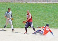 Sgt. Boyd Thomasson, Alpha Company, 101st Brigade Support Battalion, 1st Armored Brigade Combat Team, 1st Inf. Div. and coach of 'Collateral Damage', right, slid into second base before Spc. Mike Rasmussen, Bravo Battery, 1st Battalion, 7th Field Artillery Regiment, 2nd Armored Combat Brigade Team, 1st Inf. Div. of the 'Bravo Bulls', left, could get the ball to 'Bravo Bulls' second baseman Spc. Dennis Padgett, Bravo Company, 1st Bn., 7th FA Regt., 2nd ABCT, 1st Inf. Div., center, during the Midnight Madness Softball Tournament June 20 at Sacco Softball Fields.