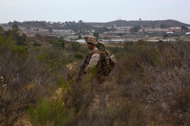 Corporal Russell Robertson, a squad leader assigned to Company I, 3rd Battalion, 5th Marine Regiment, patrols through brush during the patrolling portion of the 1st Marine Division Super Squad Competition aboard Marine Corps Base Camp Pendleton, Calif., June 30, 2015. The Marines and Sailors tested their abilities to conduct infantry operations for the title of super squad.