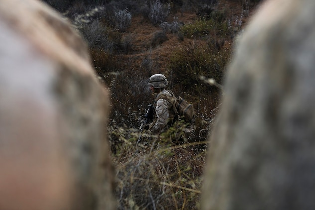 A Marine assigned to Company I, 3rd Battalion, 5th Marine Regiment, patrols through brush during the patrolling portion of the 2015 1st Marine Division Super Squad Competition aboard Marine Corps Base Camp Pendleton, Calif., June 30, 2015. The Marines and Sailors tested their abilities to conduct infantry operations for the title of super squad.