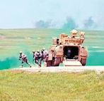 Co. A, 1st Bn., 18th Inf. Regt., move rapidly into position after dismounting from their Bradley Fighting Vehicle.