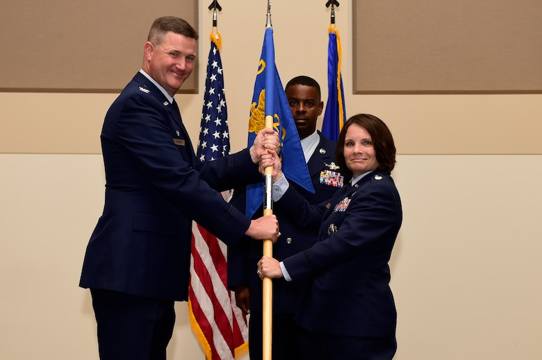 Col. Michael Jackson, 460th Operations Group commander, left; presents the 460th Space Wing guidon to Lt. Col. April Wimmer, right; symbolizing her assumption of command as the 2nd Space Warning Squadron commander July 7, 2015, on Buckley Air Force Base, Colo. Wimmer became the commander of the 2nd SWS after serving as the operations officer at the 533rd Training Squadron, Vandenberg AFB, Cali. (U.S. Air Force photo by Staff Sgt. Stephany Richards/Released)