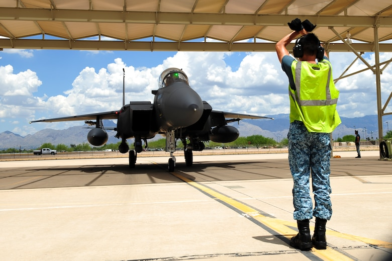 Republic of Singapore Air Force Assistant Expert Luo Youyang, 428th Fighter Squadron crew chief, taxis an F-15SG fighter jet from the 428th Fighter Squadron located at Mountain Home Air Force Base, Idaho, under a sunshade at Davis-Monthan Air Force Base, Ariz., July 7, 2015. The 428th FS was established by the Peace Carvin V program, a partnership between the U.S. Air Force and Republic of Singapore Air Force to training the RSAF pilots, weapons systems operators, ground control intercept officers, and maintainers to be able to operate their fleet. (U.S. Air Force photo by Airman 1st Class Chris Drzazgowski/Released)