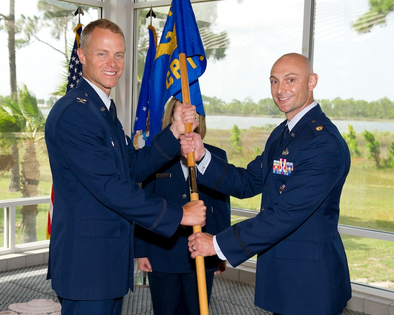 Colonel Derek C. France, the 325th Fighter Wing commander, passes the 325th Comptroller Squadron guidon to Maj. Jared Mitchell, 325th CPTS commander, during a change of command ceremony June 30. Mitchell replaces Maj. Timothy Fast who will go on to serve as the 82nd Comptroller Squadron commander at Sheppard AFB, Texas. (U.S. Air Force photo by Senior Airman Alex Echols/Released)
