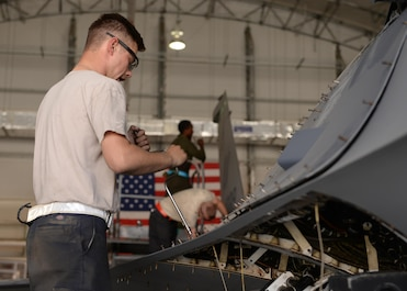 U.S. Air Force Senior Airman Nicolas Smith, 455th Expeditionary Aircraft Maintenance Squadron F-16 aircraft maintainer, works on a jet during a phase inspection July 7, 2015, at Bagram Airfield, Afghanistan. The phase inspection team, who has been deployed to BAF for two months, is working on their 12th phase inspection that occurs after a jet has reached 400 flying hours. (U.S. Air Force photo by Senior Airman Cierra Presentado/Released)