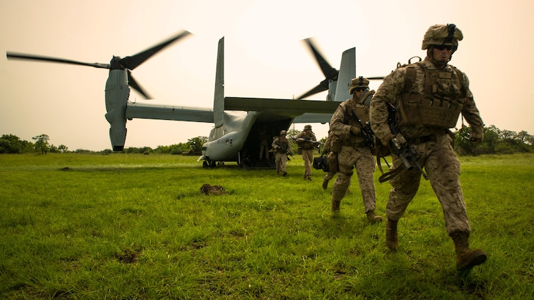 U.S. Marine Lance Cpl. Joshua Ewald, right, a member of Special-Purpose Marine Air-Ground Task Force Crisis Response-Africa, runs off an MV-22B Osprey during a training mission outside Accra, Ghana, April 13, 2015. The Marines used the vertical landing capabilities of the Osprey to secure a landing zone at their training site before securing a series of nearby compounds.