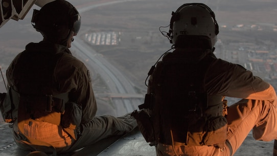 Two crew chiefs with Marine Heavy Helicopter Squadron (HMH) 466 look out the back door of a CH-53E Super Stallion en route to Marine Corps Base Camp Pendleton, California, July 2. The air crew conducted night fast-rope training with Marines from Golf Company, Battalion Landing Team 2nd Battalion, 1st Marine Regiment.