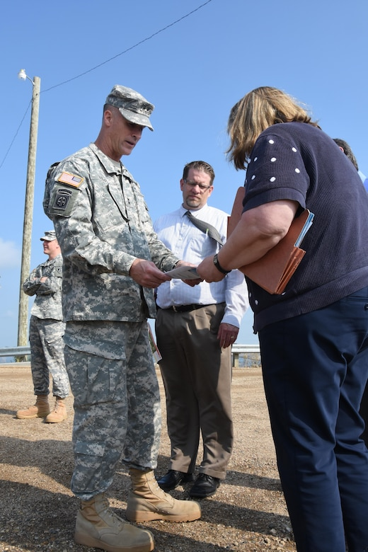 Bonnie Greenleaf, Devils Lake flood risk management project manager, briefs Mississippi Valley Division commander Maj. Gen. Michael Wehr on features of the project during a tour of the area during his North Dakota visit July 6-8, 2015. The Devils Lake basin is a 3,810 square-mile sub-basin of the Red River of the North with no natural outlet until lake levels reach an elevation 1,458, at which it flows through Tolna Coulee into the Sheyenne River. Maj. Gen. Wehr received an orientation of the Devils Lake Basin prior to attending Devils Lake Executive Committee, or DLEC, meeting July 8, 2015. The DLEC, co-chaired by the commander of the Mississippi Valley Division and the governor of North Dakota,  is comprised of representatives from more than 20 Federal, State, tribal, local agencies and governmental entities.