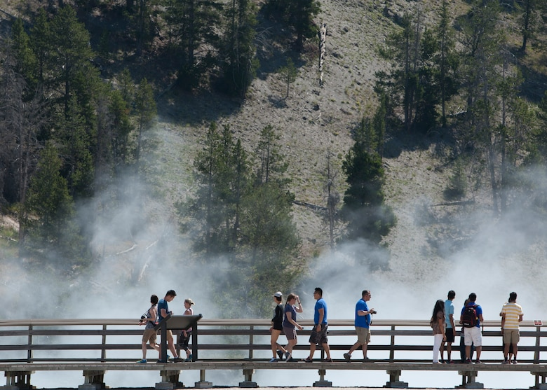 This photo panorama created from three separate images, depicts a crowd of spectators viewing the eruption of Old Faithful Geyser at Yellowstone National Park, Wyo., July 4, 2015. Airmen and civilians from F.E. Warren Air Force Base were on an Outdoor Recreation trip that explored the natural features of Yellowstone and Grand Teton National Park for the July 4th weekend. (U.S. Air Force photo by Lan Kim)