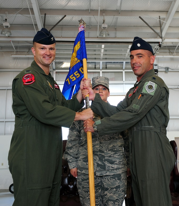 U.S. Air Force Col. Ryan Rogers, 55th Electronic Group commander, passes the 755th Operations Support Squadron's guidon to Lt. Col. Joshua Koslov, 755th OSS commander, during a change of command ceremony at Davis-Monthan Air Force Base, Ariz., July 9, 2015. The commander is responsible for group support functions such as intelligence, current operations, plans and exercises, weapons and tactics, and operational support. (U.S. Air Force photo by Airman 1st Class Chris Drzazgowski/Released)