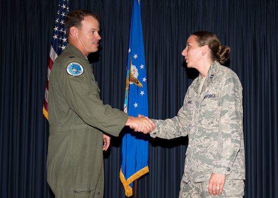 Col. Byron Anderson, 366th Fighter Wing vice commander, presents Capt. Judene Rohde, installation project officer of the campaign on base, with his commander's coin for her hard work leading the Air Force Assistance Fund campaign at Mountain Home Air Force Base, Idaho, July 8, 2015. MHAFB was able to make 100 percent contact with all personnel on base this year. (U.S. Air Force photo by Airman 1st Class Jeremy L. Mosier)