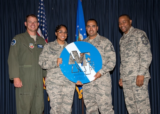 Col. Byron Anderson, 366th Fighter Wing vice commander, and Chief Master Sgt. David Brown, 366th FW command chief, present members of the 366th Medical Group with the large Blue and White Coin at Mountain Home Air Force Base, Idaho, July 8, 2015. The 366th Medical Group had the highest Air Force Assistance Fund participation rate on base. (U.S. Air Force photo by Airman 1st Class Jeremy L. Mosier)