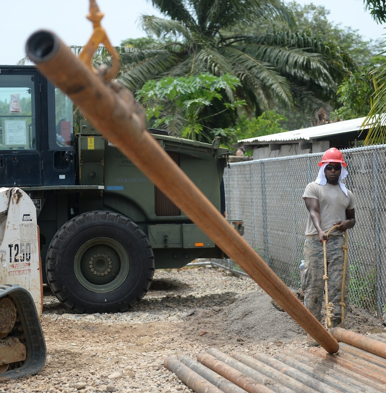 U.S. Air Force Senior Airman Malcolm Stone, 823rd Expeditionary RED HORSE Squadron pavements and construction equipment operator, out of Hurlburt Field, Fla., directs a piece of drilling steel at the well site in Honduras Aguan, Honduras, July 7, 2015. This was the last piece of steel needed to complete initial drilling of the well. The well is one of multiple projects going on in and around Trujillo as part of NEW HORIZONS Honduras 2015 training exercise. NEW HORIZONS was launched in the 1980s and is an annual joint humanitarian assistance exercise that U.S. Southern Command conducts with a partner nation in Central America, South America or the Caribbean. The exercise improves joint training readiness of U.S. and partner nation civil engineers, medical professionals and support personnel through humanitarian assistance activities. (U.S. Air Force photo by Capt. David J. Murphy/Released)