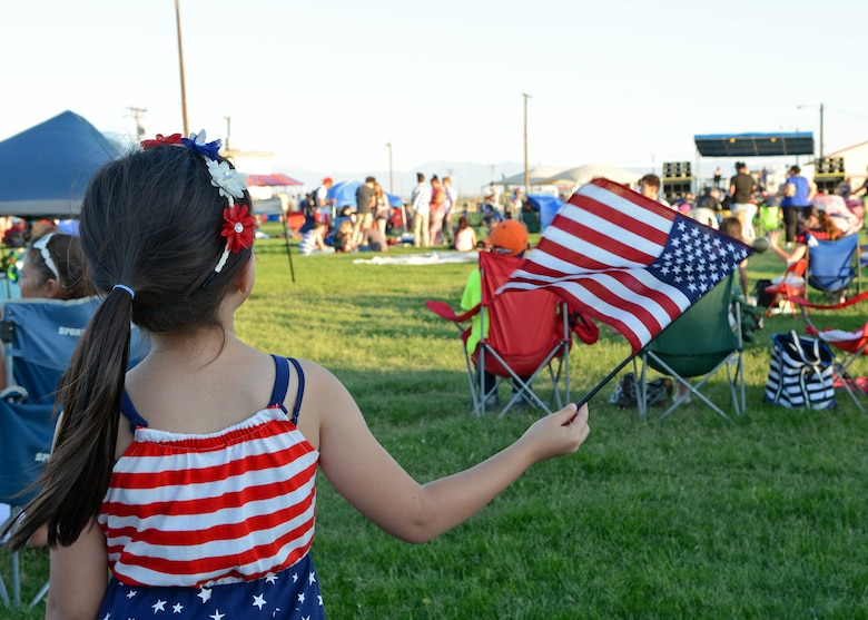 A child shows off her patriotism while listening to live entertainment that was provided for the base community during the 2015 Freedom Fest July 4 at Wings and Roberts Fields. (U.S. Air Force photo by Jet Fabara)