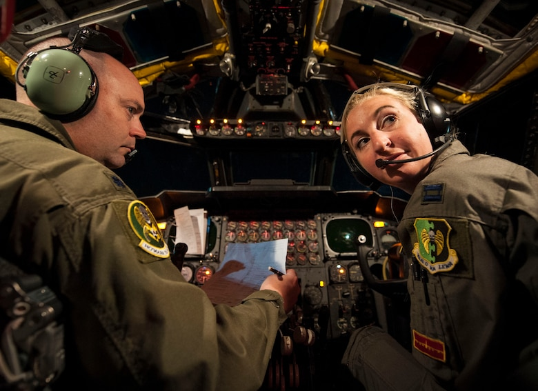 Lt. Col. Monte Wiley, 69th Bomb Squadron pilot (left), completes pre-flight check as Capt. Kristin Nelson, 23rd BS pilot (right), listens to input from other crew members inside their B-52H Stratofortress at Minot Air Force Base, N.D., July 9, 2015. Wiley and Nelson piloted one of two B-52H Stratofortresses participating in a 16-hour mission to support an air show in Rio Negro, Colombia. (U.S. Air Force photo/Senior Airman Stephanie Morris)