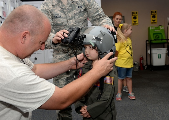 Cody Dugger helps his son, Jaxon, put on a flight helmet equipped with nightvision goggles at the 97th Operations Support Squadron, Altus Air Force Base, Oklahoma, June 26, 2015. Jaxon was diagnosed with Ewing's sarcoma when he was two years old. (U.S. Air Force photo by Airman 1st Class Kirby Turbak)