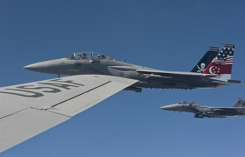 Two F-15E Strike Eagles from Mountain Home Air Force Base, Idaho, fly alongside the wing of a KC-135 Stratotanker from Fairchild Air Force Base, Wash., during a refueling mission June 25, 2015, over the Inland Northwest.  During the mission some of the F-15E Strike Eagles were flown by Republic of Singapore air force pilots in training, as well as American pilots. (U.S. Air Force photo/Staff Sgt. Veronica Montes)