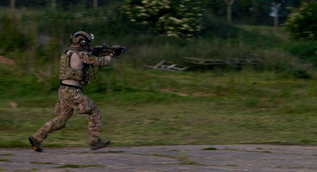 An Airman from the 321st Special Tactics Squadron fires simulated rounds from his weapon while participating in an exercise June 25, 2015, at RAF Sculthorpe in Norfolk, England. The 321st STS regularly train on how to infiltrate a potentially hostile area using the Fast Rope Insertion Extraction System. (U.S. Air Force photo/Senior Airman Victoria H. Taylor)