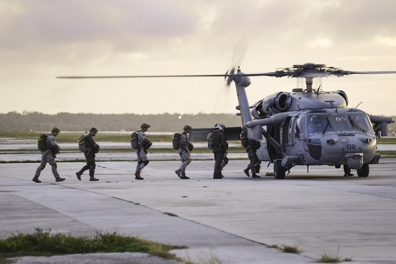 Members of the 736th Security Forces Squadron board an MH-60 Sierra, assigned to Helicopter Sea Combat Squadron 25, July 3, 2015, at Andersen Air Force Base, Guam. HSC-25 provides vital airlift support to the 736th SFS, assisting with their quarterly static line parachute operations. (U.S. Air Force photo/Senior Airman Katrina M. Brisbin)