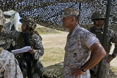Colonel Phillip N. Frietze, Commanding Officer, Headquarters Regiment, 1st Marine Logistics Group, speaks with Marines of Combat Logistics Battalion 11, Headquarters Regiment, 1st Marine Logistics Group, during a loading exercise aboard Red Beach Camp Pendleton, Calif., June 23, 2015. This loading exercise reinforces the Marine Corps' role as an amphibious force in readiness by maintaining capabilities through realistic training. (U.S. Marine Corps photo by Lance Cpl. Lauren Falk/Released)