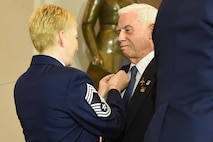 Chief Master Sgt. Nicole Johnson, the executive assistant to the chief master sgt. of the Air Force, presents the commemorative Vietnam veteran lapel pin to retired Col. Michael Brazelton during the Congressional Commemoration for the 50th Anniversary of the Vietnam War July 8, 2015, in the Emancipation Hall of the U.S. Capitol in Washington. (U.S. Air Force photo/Staff Sgt. Carlin Leslie)