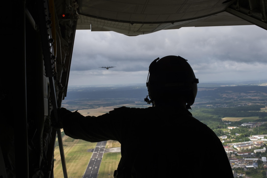 Airman 1st Class Austin Lilly, a 37th Airlift Squadron loadmaster, looks out the back of a C-130J Super Hercules, ensuring paratroopers can safely exit the aircraft during International Jump Week, July 8, 2015, at Ramstein Air Base, Germany. International Jump Week is an annual event that gives paratroopers the opportunity to practice high altitude, low opening and static line jumps. Pilots, loadmasters and parachute riggers were also able to train during the week. (U.S. Air Force photo/Senior Airman Damon Kasberg)