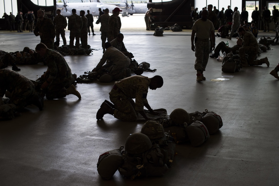 Service members pack parachutes prior to jumping during International Jump Week, July 8, 2015, at Ramstein Air Base, Germany. International Jump Week is an annual event providing paratroopers the opportunity to practice high altitude, low opening and static line jumps. Pilots, loadmasters and parachute riggers were also able to train during the week. Supporting units at the drop zone included U.S. Air Force and Army personnel, air traffic controllers, and medical teams. (U.S. Air Force photo/Senior Airman Damon Kasberg)