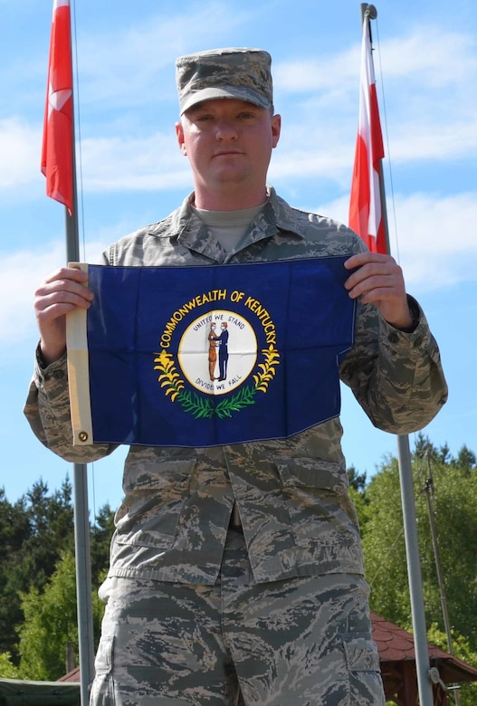 Senior Airman Steven Adkins, a broadcast journalist assigned to American Forces Network, Spangdahlem Air Base, Germany, proudly displays his state flag June 7, 2015, during an assignment for exercise Saber Strike 15 in the Drawsko Pomorskie Training Area in Poland. The flag was given to Adkins by his grandfather, a retired Air Force veteran, who kept a ledger of every location he traveled to with the flag during his last six years in the service, and then gave it to Adkins to carry on the tradition. (U.S. Army photo/Sgt. Brandon Anderson)