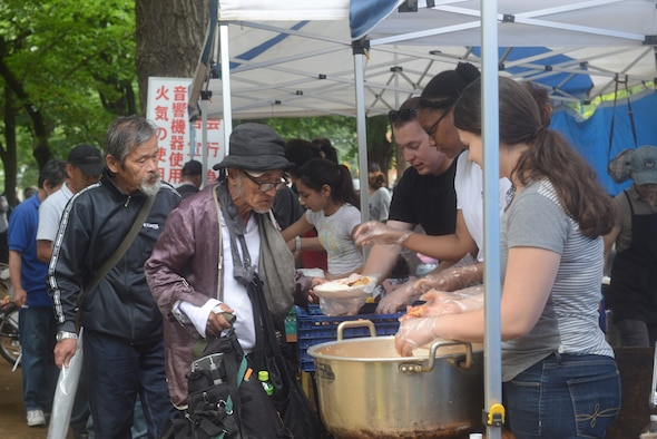 Members from Yokota Air Base, Japan, and members of a local church serve food to the homeless at Ueno Park, Tokyo Japan, June 26, 2015. The base chapel has received multiple commendations, including the Zenko-Kai award, for their participation in homeless outreach events. (U.S. Air Force photo by Airman 1st Class David C. Danford/Released)