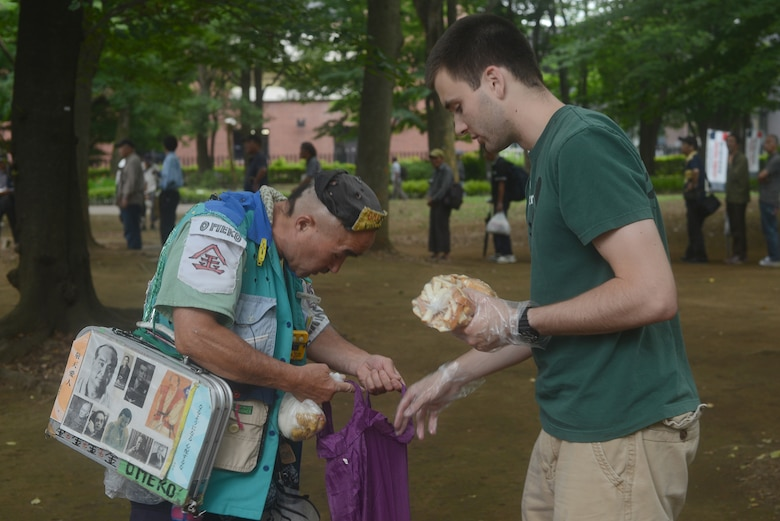 Patrick Cole hands out bread to the homeless at Ueno Park, Tokyo Japan, June 26, 2015. More than 400 people were fed at the homeless outreach event. (U.S. Air Force photo by Airman 1st Class David C. Danford/Released)