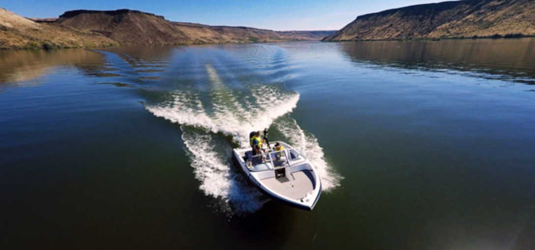 Senior Airman Jaye Legate, 366th Fighter Wing Public Affairs broadcaster, drives a ProCraft towing boat at C.J. Strike Reservoir, Idaho, June 26, 2015. The Air Force Marina at C.J. Strike Dam offers many rental options such as paddleboards, kayaks and various types of boats. (Courtesy photo by Samuel Morse)