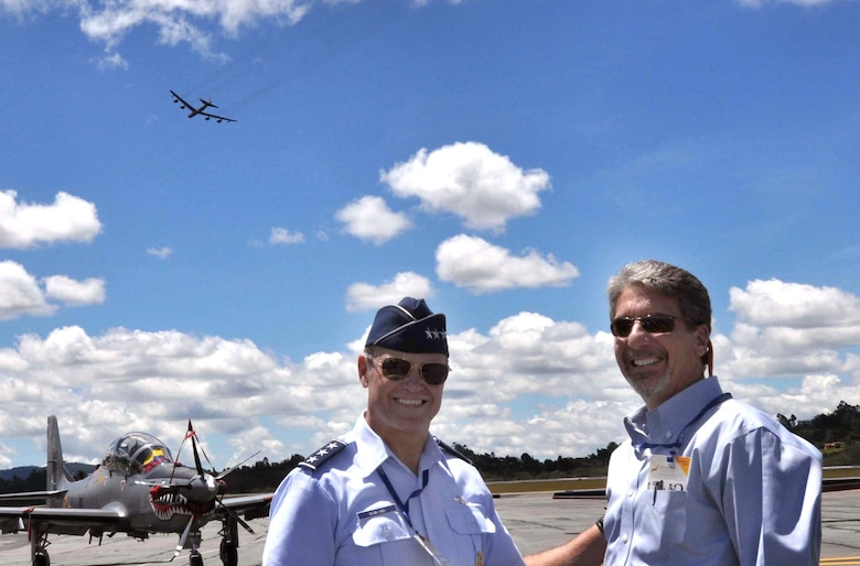 Kevin Whitaker, United States Ambassador to Colombia, poses with Lt. Gen. Chris Nowland, Commander 12th Air Force (Air Forces Southern) as a U.S. Air Force B-52 Stratofortress completes a flyover demonstration at the Colombian International Air Festival, July 9, 2015 in Rionegro, Colombia. The aircraft, which can be seen in the background, took off from its home station at Minot Air Force Base, N.D., to conduct a 16-hour, long-range training mission which included the flyover in Colombia. The B-52 Stratofortress is a long-range strategic aircraft capable of traveling 8,800 miles before refueling. (U.S. Air Force photo by MSgt. Kristina Newton/Released)
