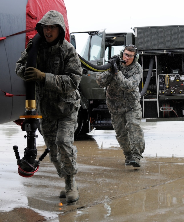 Staff Sgt. Daniel Vergun, 127th Logistics Readiness Squadron fuels technician, and Staff Sgt. Jesse Torma, 191 Maintenance Squadron crew chief, carry the fuel hose to a KC-135 Stratotanker on the flightline at Selfridge Air National Guard Base, Mich., July 9, 2015. Fully loaded, a KC-135 can hold up to 203,000 pounds of fuel. On a typical day, the average load is around 40,000 pounds or 5,900 gallons of fuel. (U.S. Air National Guard Photo by Senior Airman Ryan Zeski/Released)
