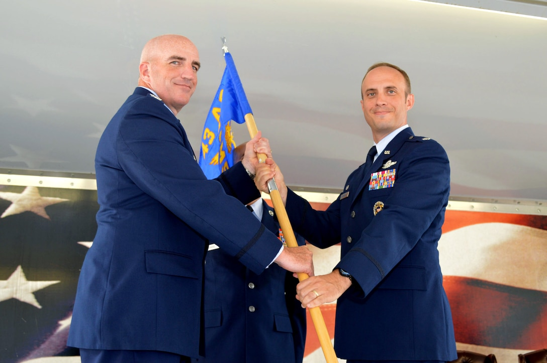 Col. Kenneth Moss, 43rd Airlift Group commander, left, passes the 43rd Air Mobility Squadron guidon to Lt. Col. David Morgan during the 43rd Air Mobility Squadron activation ceremony July 1, 2015, at Pope Army Airfield, North Carolina. Morgan assumed command of the newly established squadron composed of aircraft maintenance and aerial port Airmen and functions transferred from the inactivated 43rd Aircraft Maintenance Squadron and the 3rd Aerial Port Squadron. (U.S. Air Force photo/Marvin Krause)