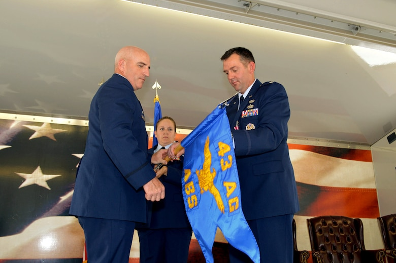 Lt. Col. Brian Ballew, 43rd Force Support Squadron commander, right, and Col. Kenneth Moss, 43rd Airlift Group commander, unfurl the 43rd Air Base Squadron guidon July 1, 2015, during the 43rd ABS redesignation and change of command ceremony at Pope Army Airfield, North Carolina. Force support and logistics Airmen and functions transferred to the newly established 43rd ABS from the inactivated 43rd Logistics Readiness Squadron and the 43rd FSS. (U.S. Air Force photo/Marvin Krause)