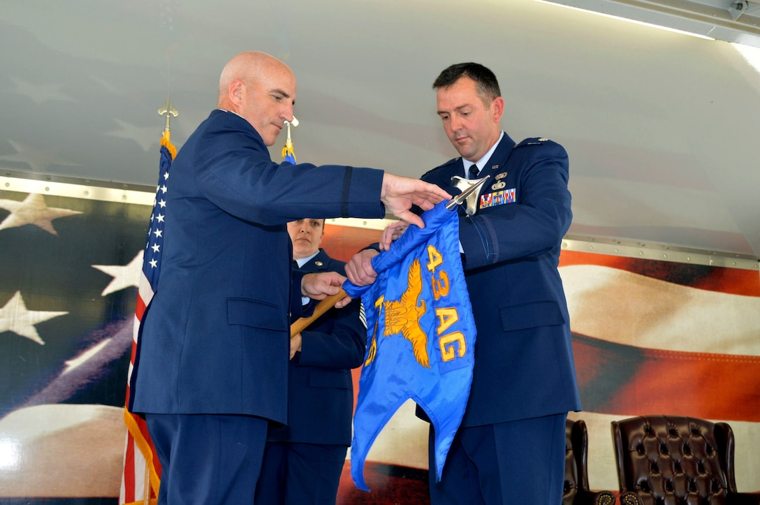 Lt. Col. Brian Ballew, 43rd Force Support Squadron commander, right, and Col. Kenneth Moss, 43rd Airlift Group commander, case the 43rd FSS guidon July 1, 2015, during the 43rd Air Base Squadron redesignation and change of command ceremony at Pope Army Airfield, North Carolina. Force support and logistics Airmen and functions transferred to the newly established 43rd ABS from the inactivated 43rd Logistics Readiness Squadron and the 43rd FSS. (U.S. Air Force photo/Marvin Krause)