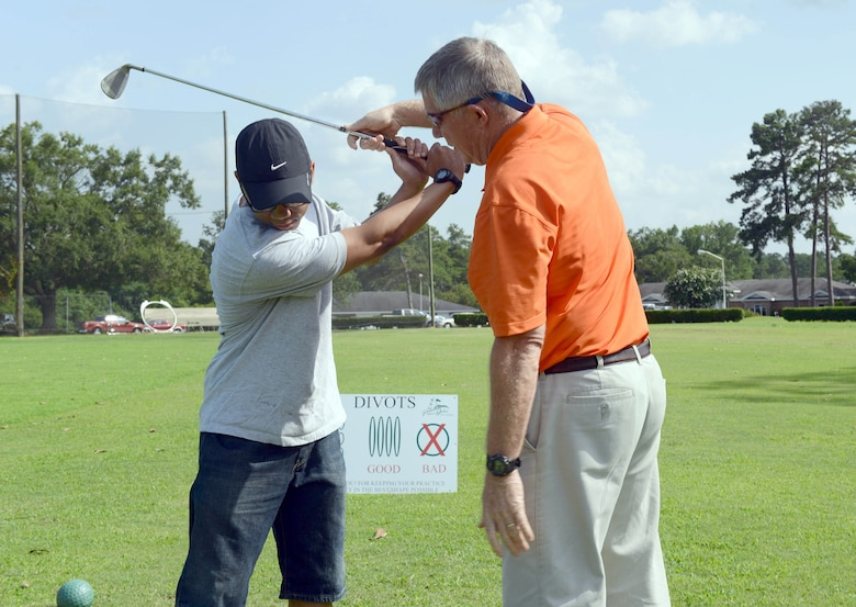 "Daniel Brewer, 5th Combat Communications Support Squadron vehicle maintenance technician, receives golf tips from Mike Baker, Pine Oaks Golf Course manager. The facility offers ""Tips from the Pro"" on Tuesdays from 5 to 6 p.m. (U.S. Air Force photo by Tommie Horton)"