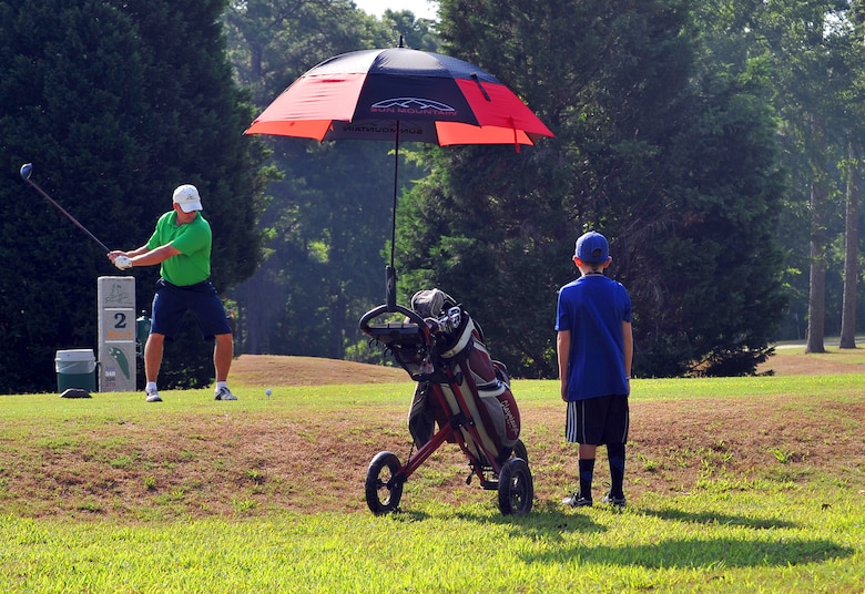 Jeff Dahlinger, a retiree, enjoys a morning of golf at Pine Oaks as 8 year-old acting caddy, Garett Rogers, looks on. The 18-hole course at Robins features 6,343 yards of golf from the longest tees for a par of 71. (U.S. Air Force photo by Tommie Horton)