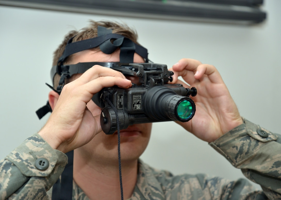 U.S. Air Force Airman Brandon Campbell, 100th Civil Engineer Squadron Power Production apprentice from Santa Rosa, Calif., adjusts the rear diopter rings to focus his night-vision goggles in preparation for night operations training during 100th CES bivouac training June 25, 2015, on RAF Mildenhall, England. Training included team movement techniques, land navigation, use of night-vision goggles and Humvee driving. (U.S. Air Force photo by Karen Abeyasekere/Released)